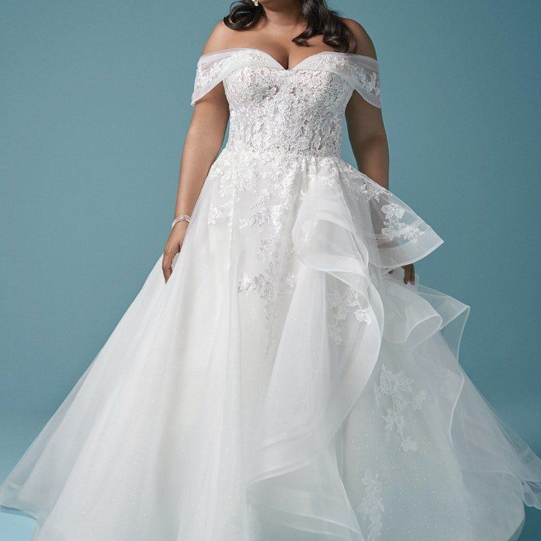 Model in off-the-shoulder tulle ball gown with lace motifs