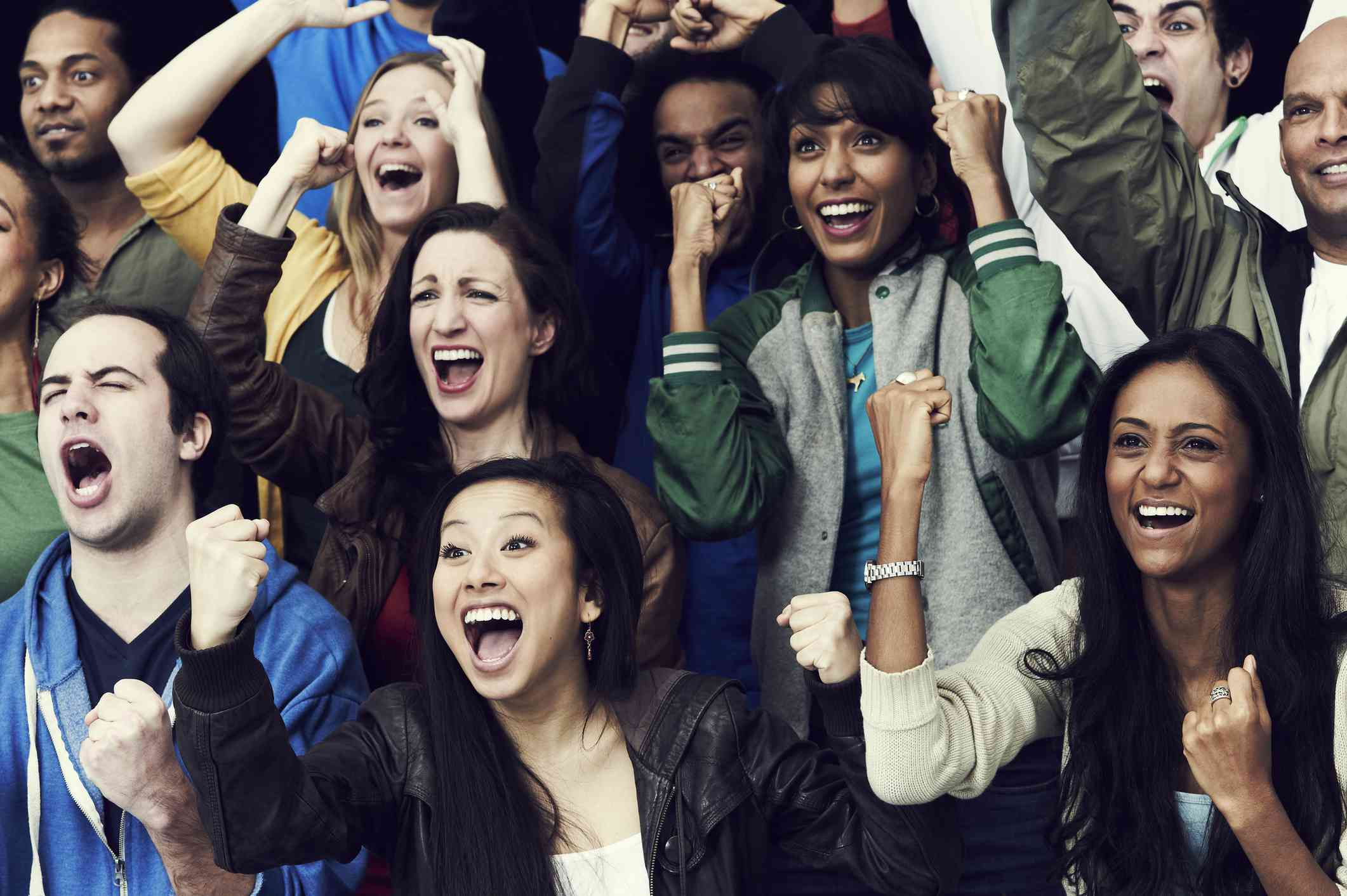 Group of young people cheering at sporting event
