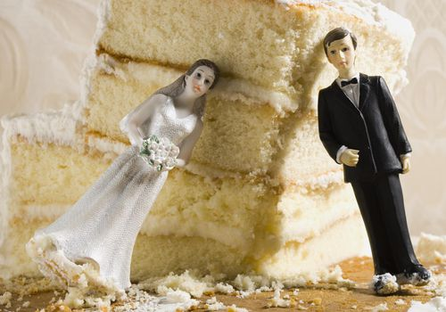 Piece of wedding cake with bride and groom cake toppers