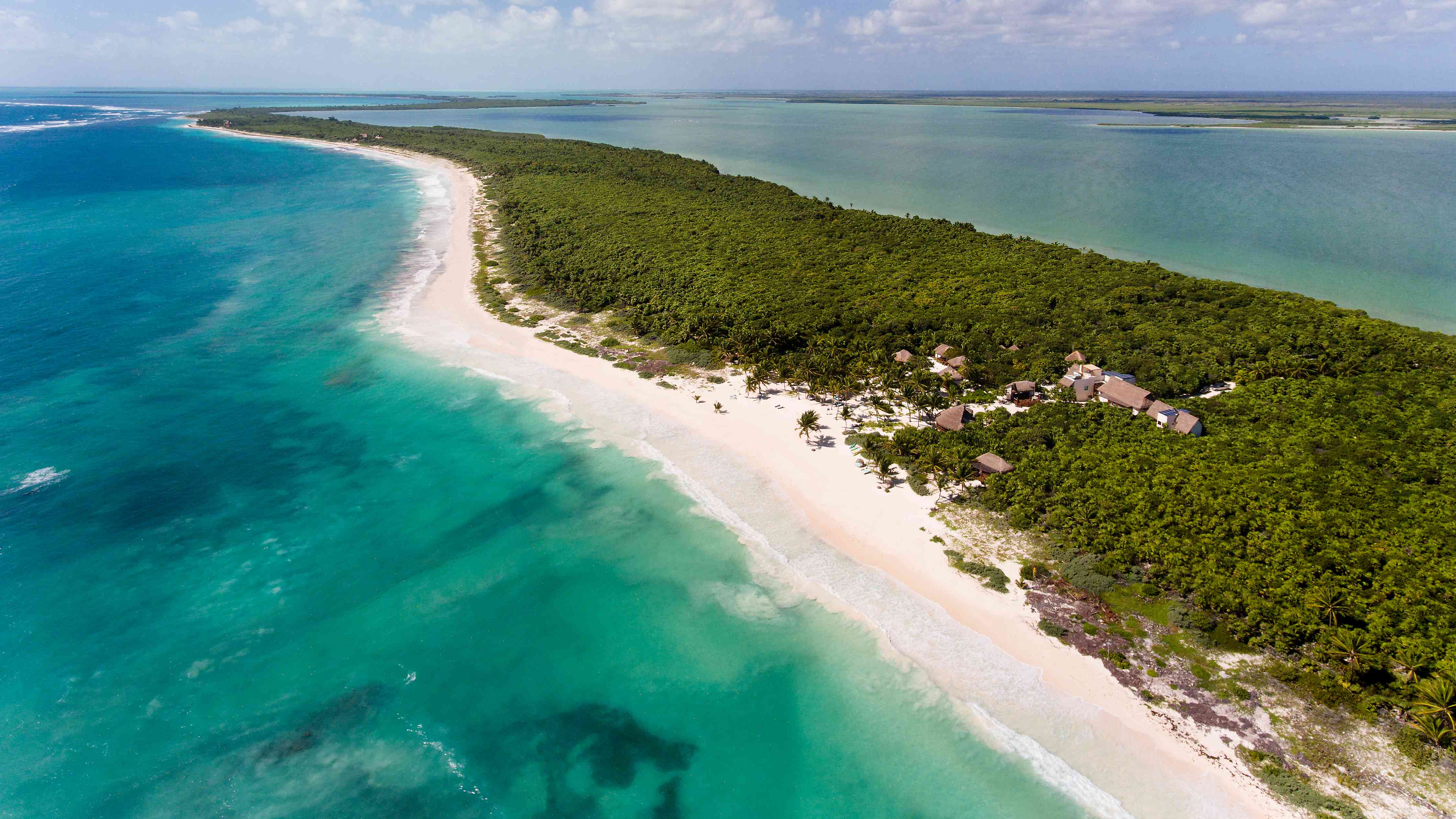 Ocean divided by sand bar with private resort