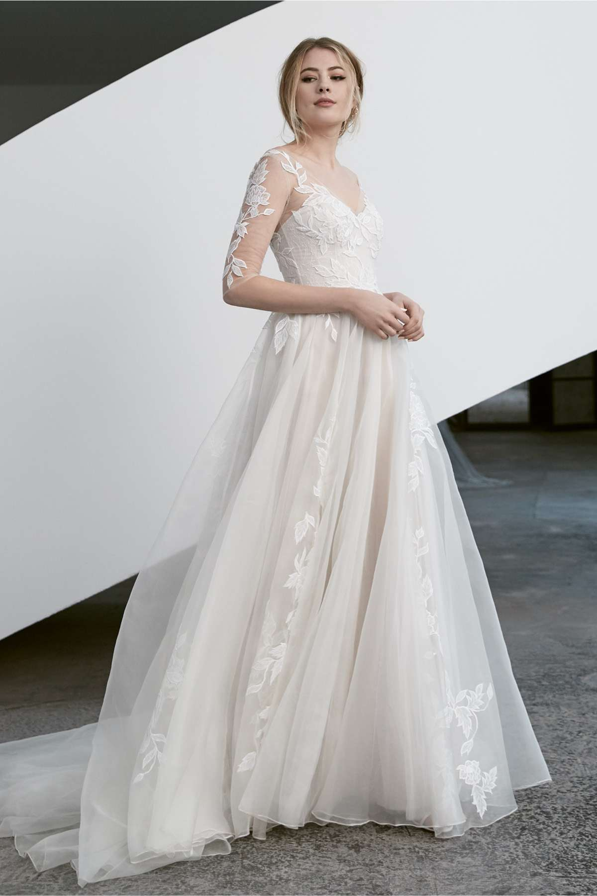 Model in ballgown with illusion bodice and sleeves with floral appliques