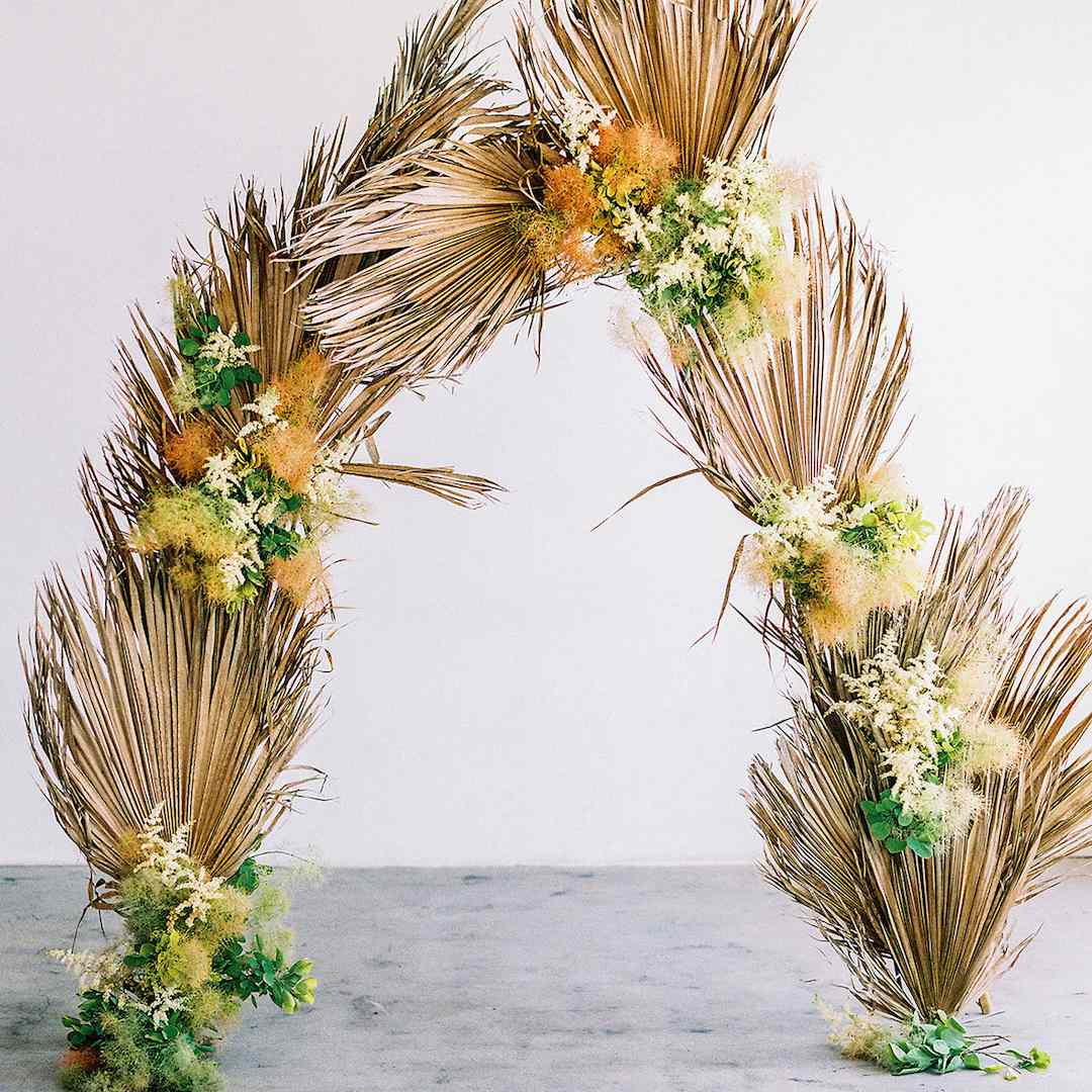Ceremony arch made of dried palm leaves, smokebush, and cream-colored astilbes