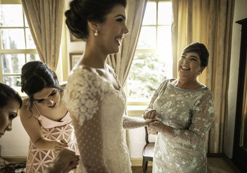 Bride holding mother's hand while bridesmaids bustle her gown