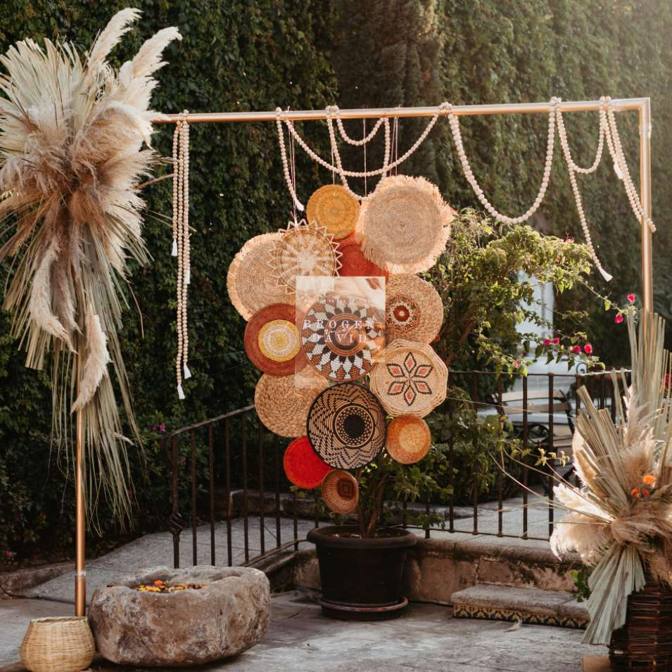 Backdrop of hanging, woven discs and dried palms