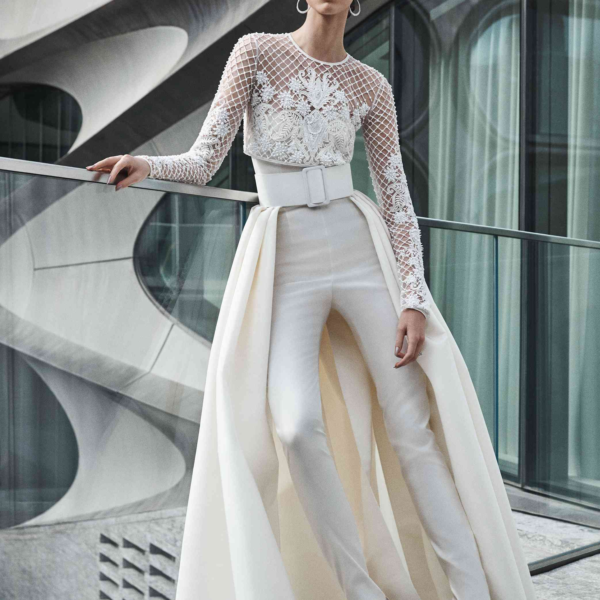 Model in jumpsuit with embroidered long-sleeve top and pleated overskirt
