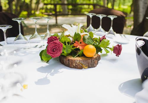 Floral centerpiece with orange on wood