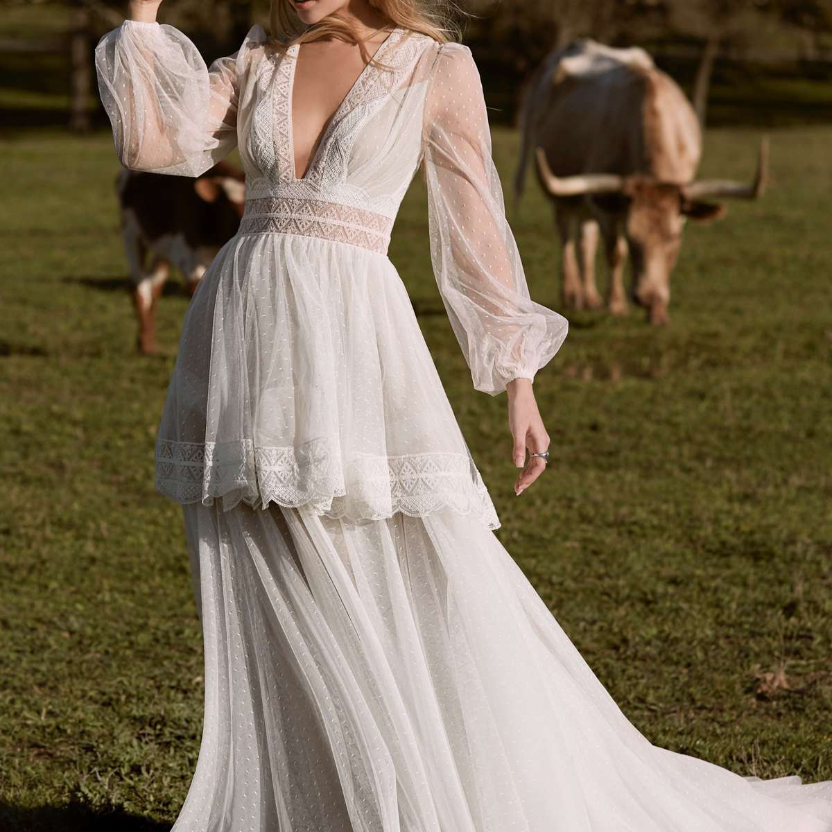 Model in a deep V-neck long-sleeve gown with border lace trim and a tiered skirt