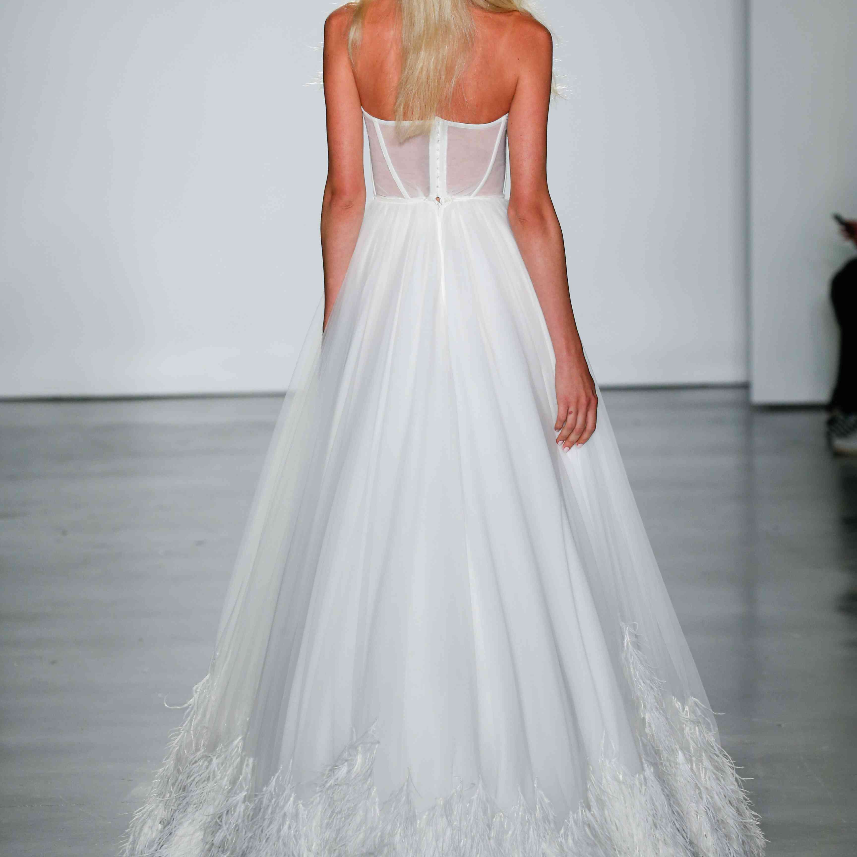 Model in strapless wedding dress with feathered hem
