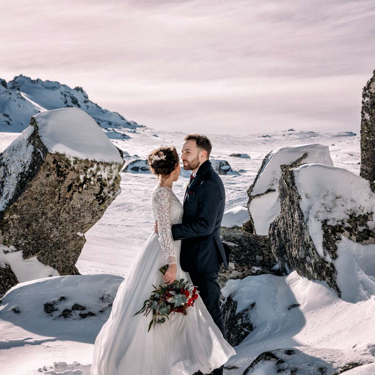 Bride and groom standing in a snowy mountainous landscape
