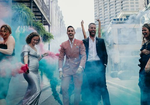 Grooms and wedding party walking down the street with colorful smoke bombs
