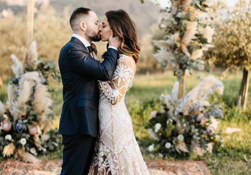 Newlyweds kissing in front of boho altar