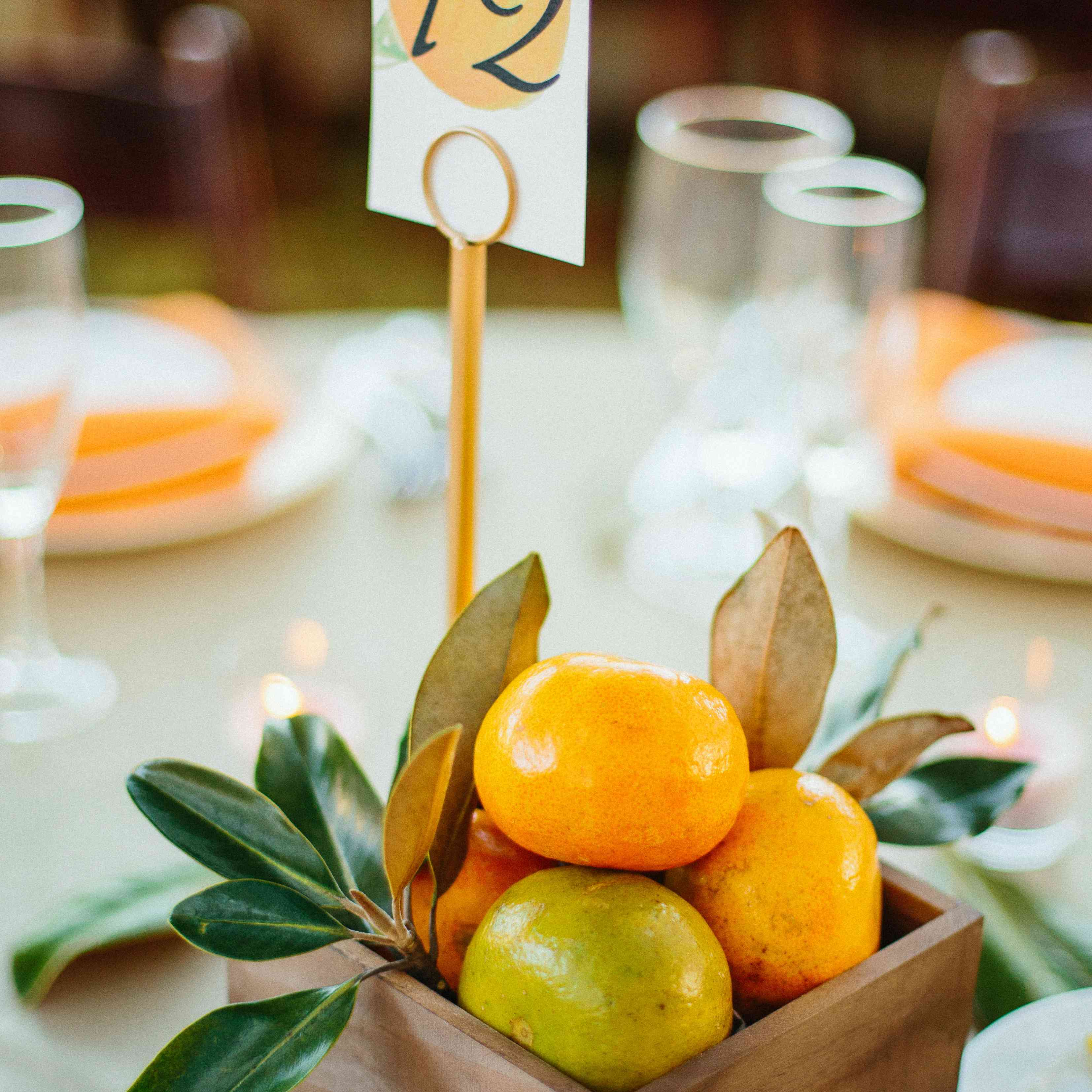 Oranges and sprigs of greenery in a wooden centerpiece