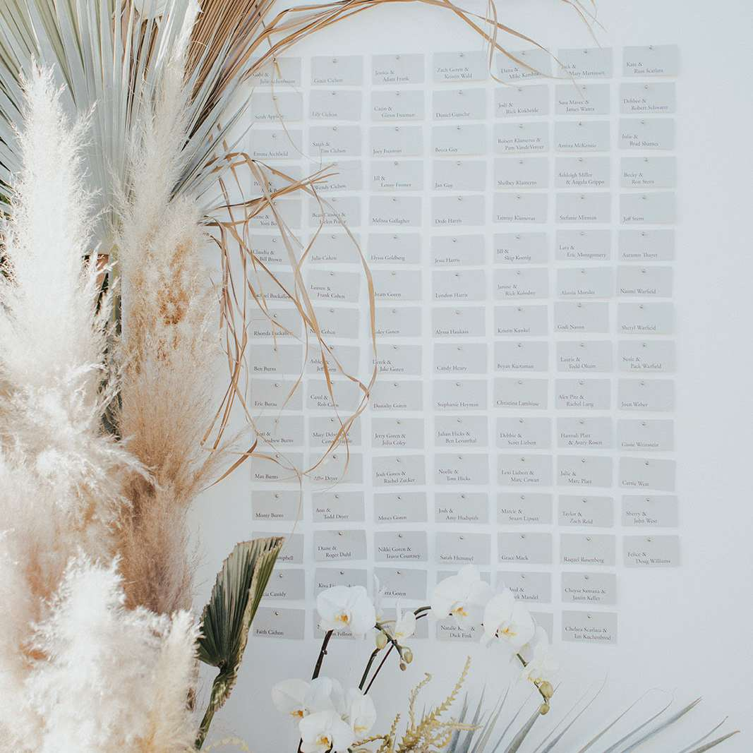 Escort card display with dried pampas grass, palm fronds, and orchid arrangement