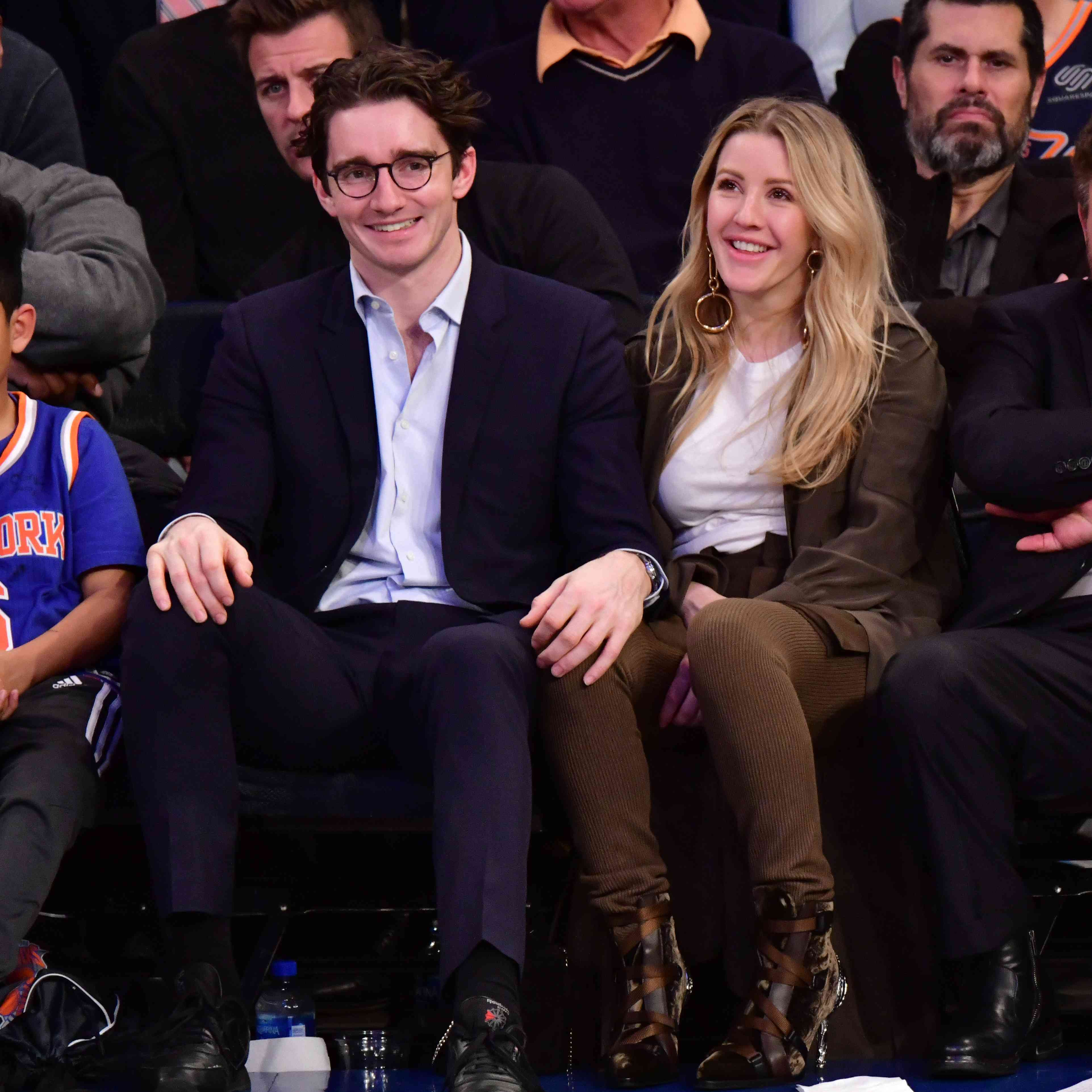 couple sitting courtside and basketball game