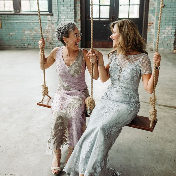 Mother of the groom and mother of the bride laughing and smiling on a swing