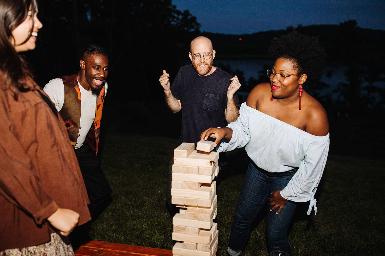 Four guests at a party playing giant Jenga