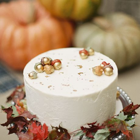 A rustic fall wedding cake embellished with autumnal leaves and metallic acorns by Nine Cakes