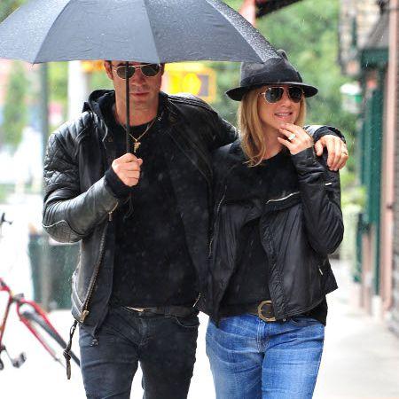 Justin Theroux (left) and Jennifer Aniston walking under a black umbrella