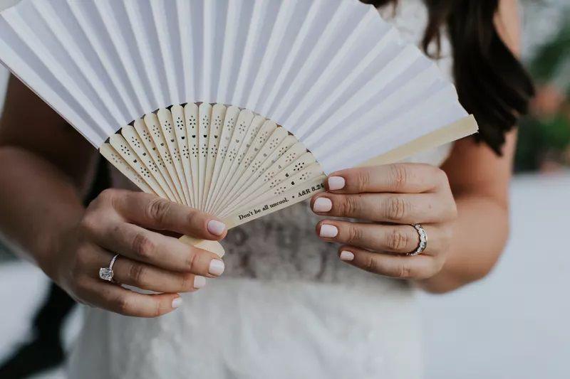 Bride's hands holding fan