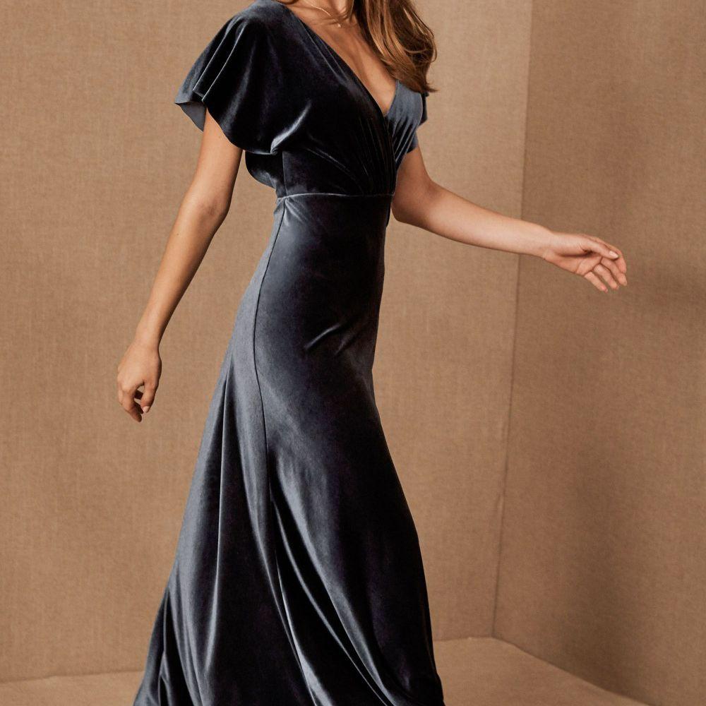 Model in a blue velvet v-neck gown with flutter sleeves