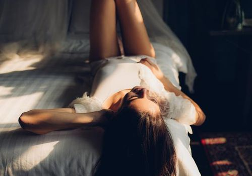 Girl laying on bed as sunlight streams in