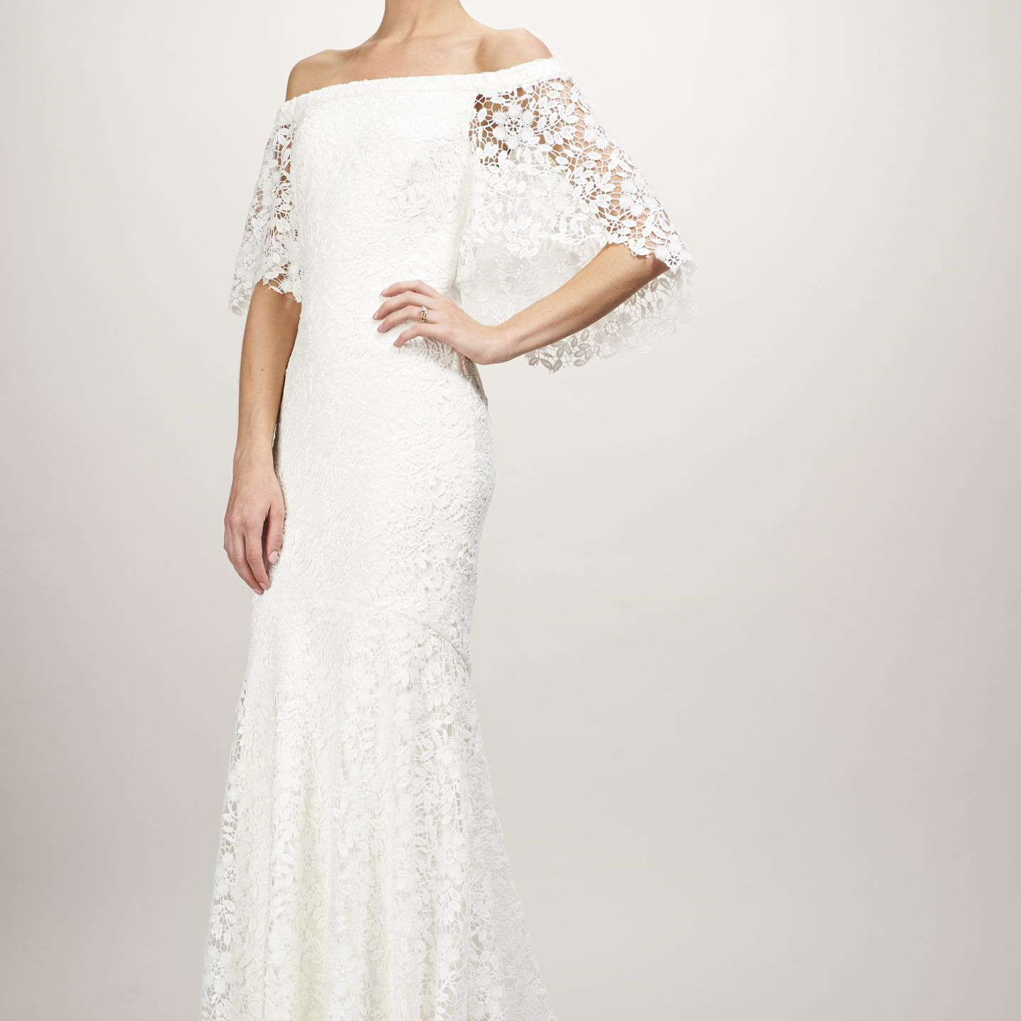Model in lace off-the-shoulder gown with winged sleeves