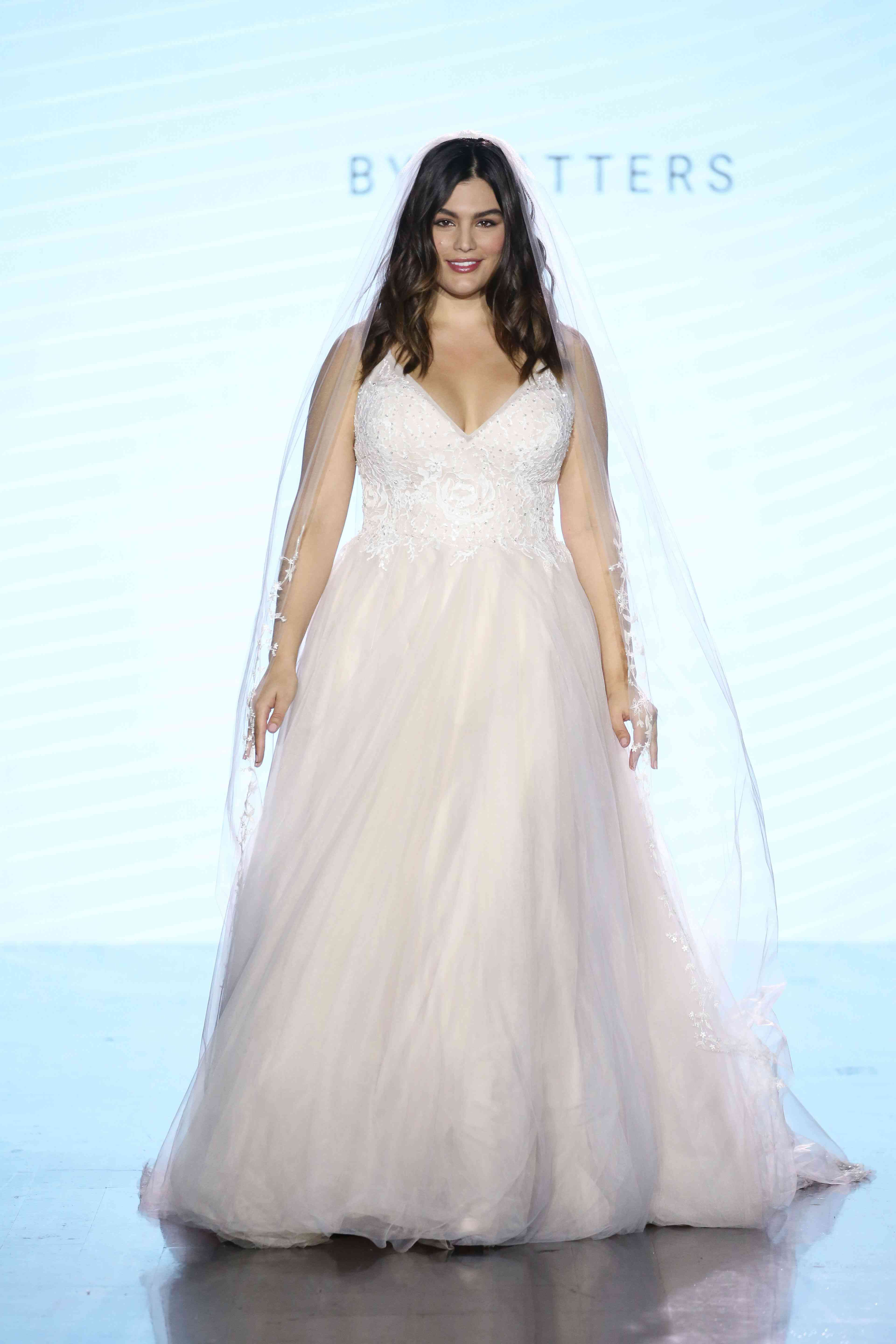 Model in V-neck ballgown with a sequined lace bodice and a tulle skirt
