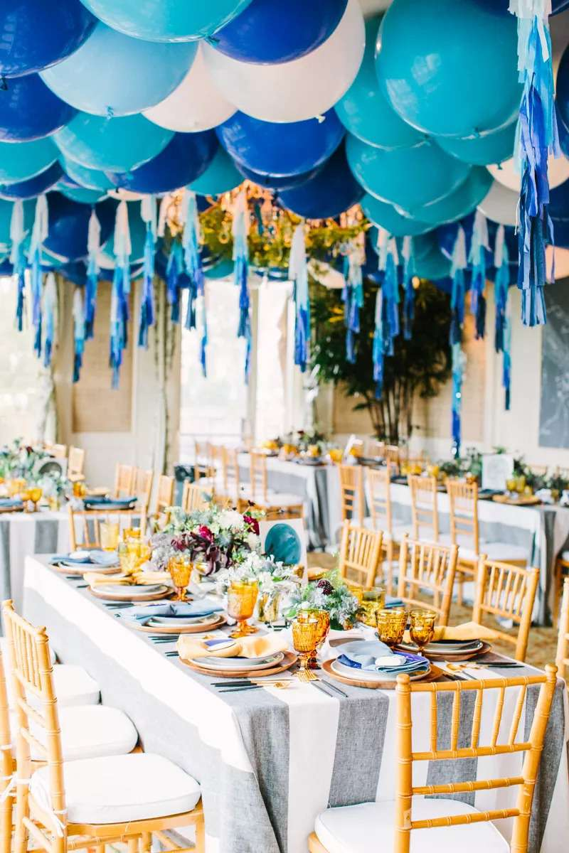 Blue balloons hanging over reception tables