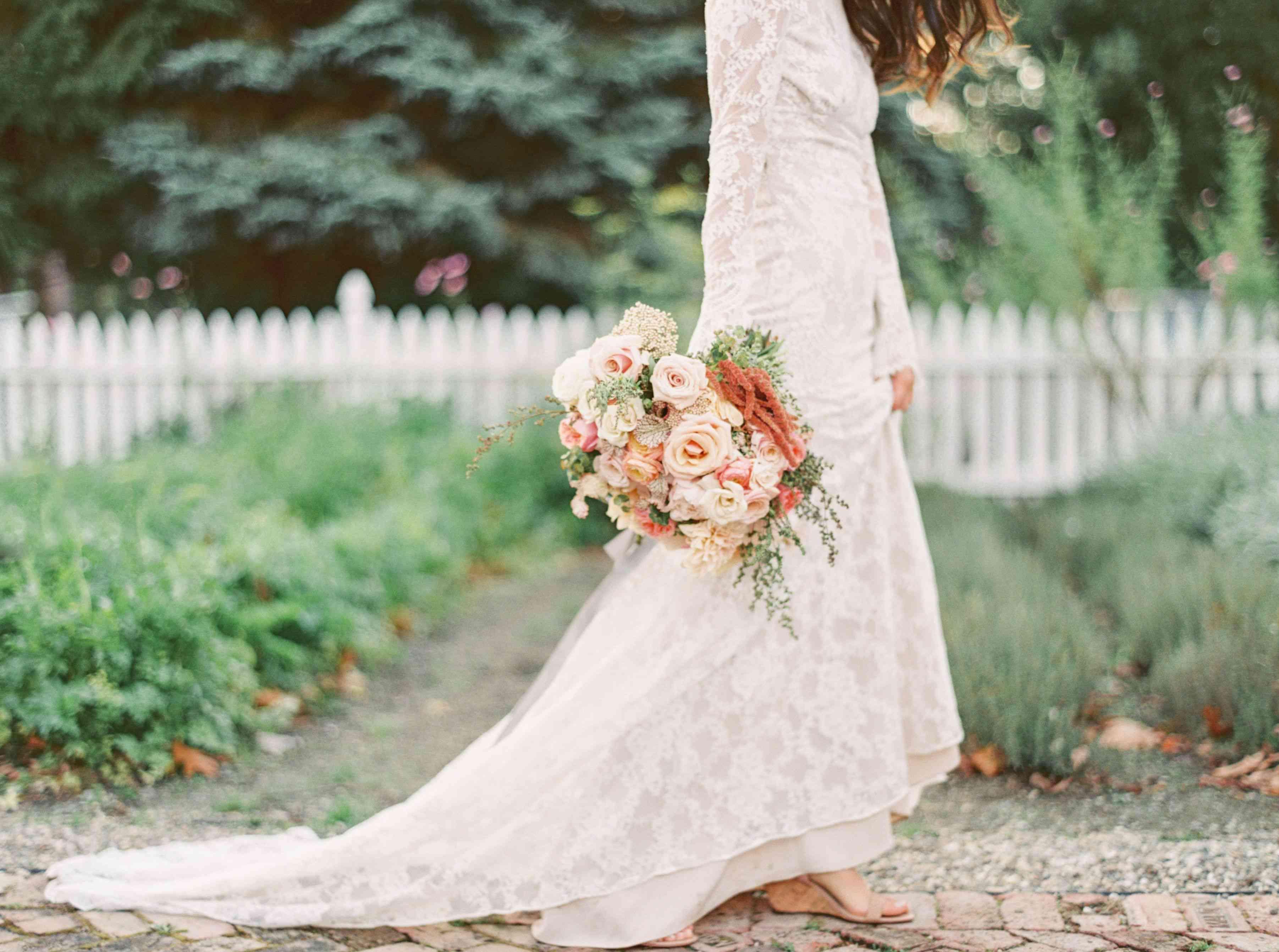 Bride holding a peach rose bouquet