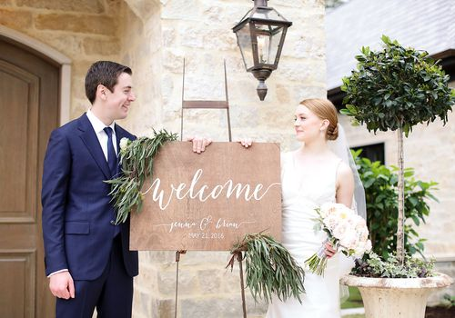 Bride and groom standing with welcome sign.