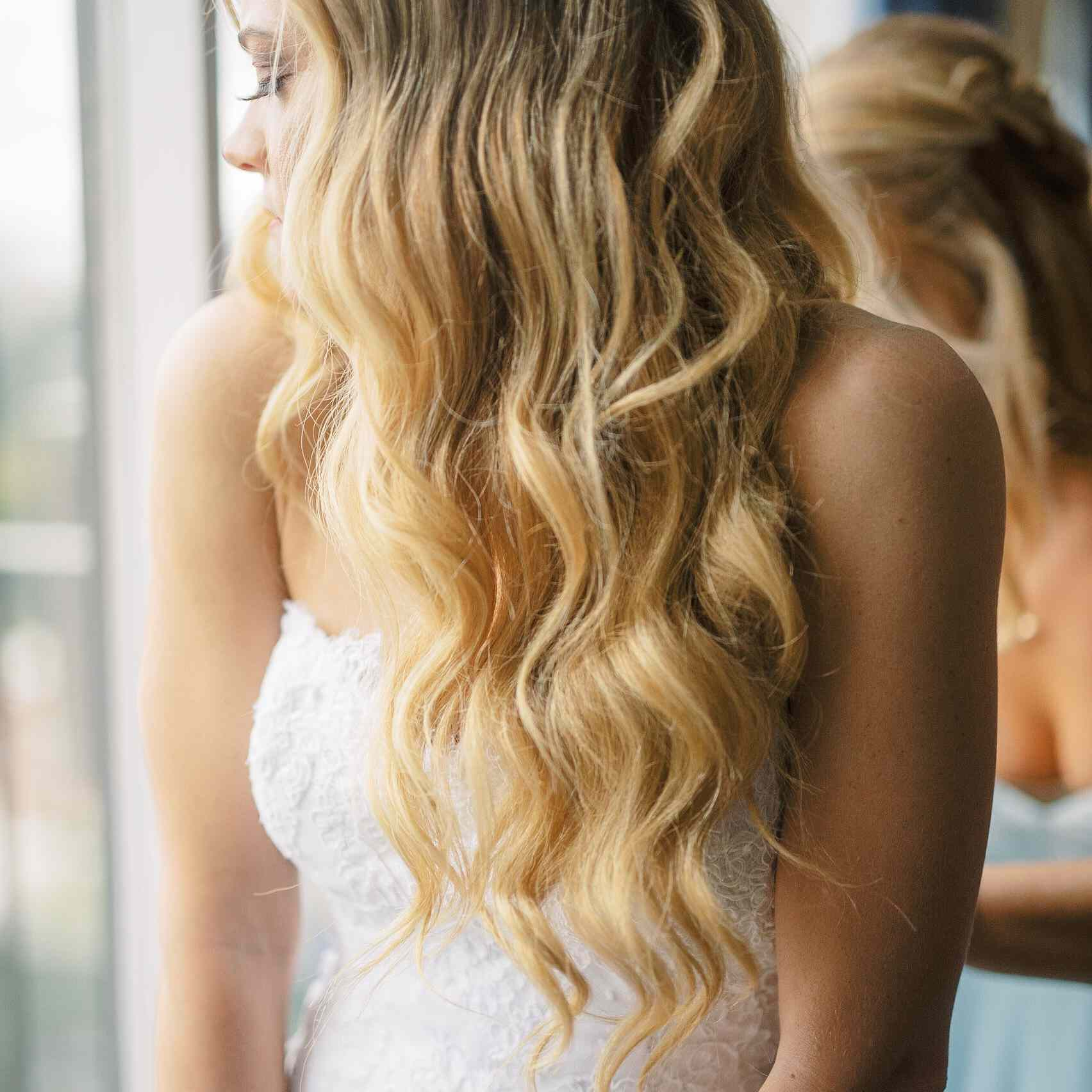 whimsical savannah wedding, bridesmaid zipping brides dress