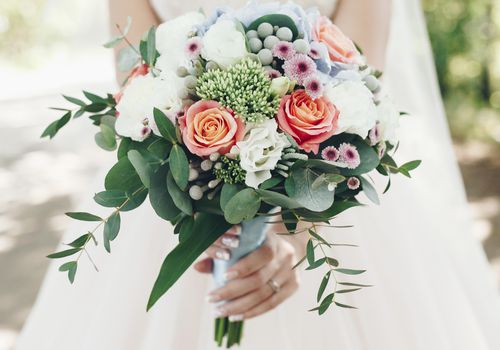 <p>A bride holding a bouquet of flowers outdoors</p>