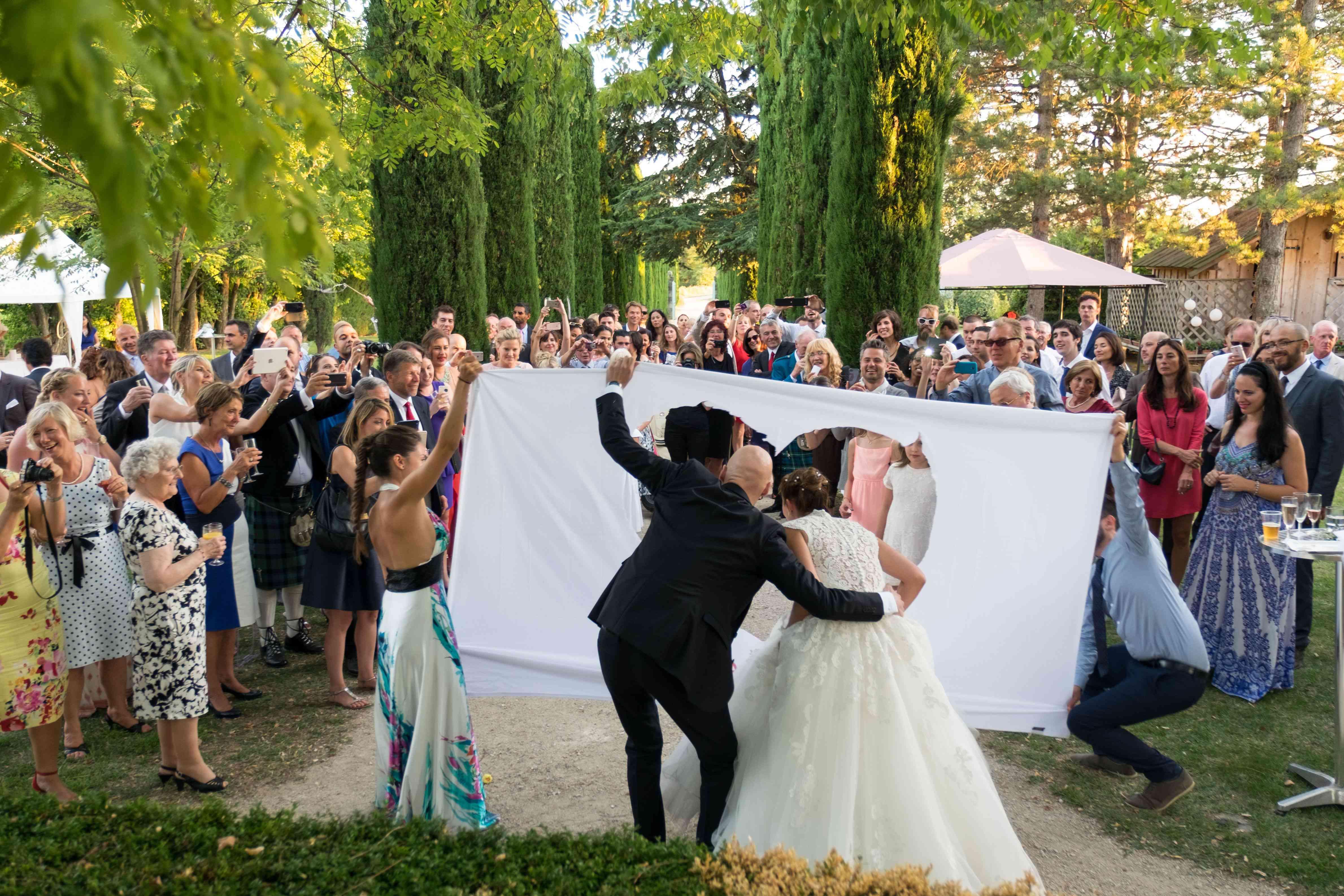 Newlyweds walking through white sheet