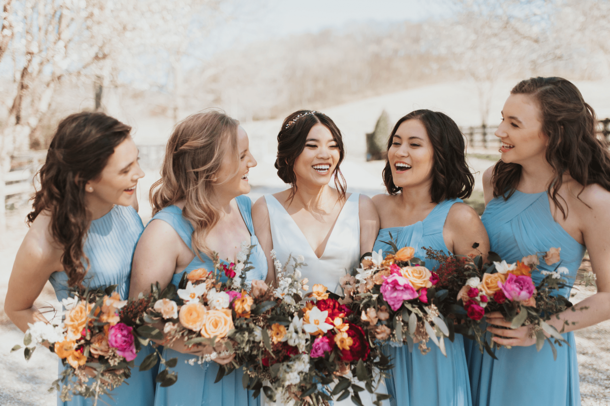 Bridesmaids in blue with bride holding bouquets