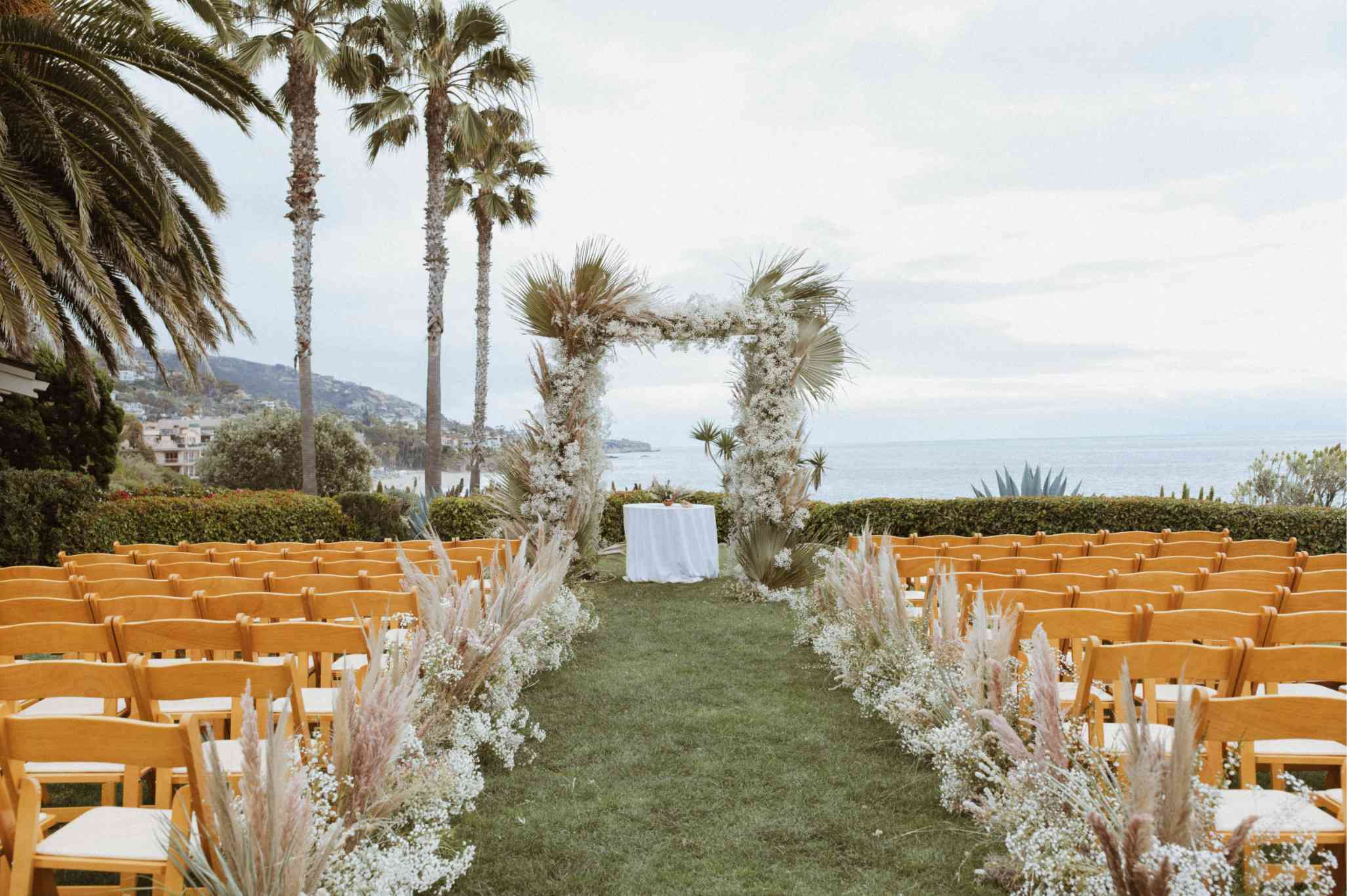Chuppah covered in pampas grass, dried palm leaves, and baby's breath