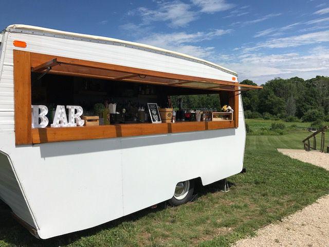 mobile bar trailer at outdoor wedding on a farm blue sky trees