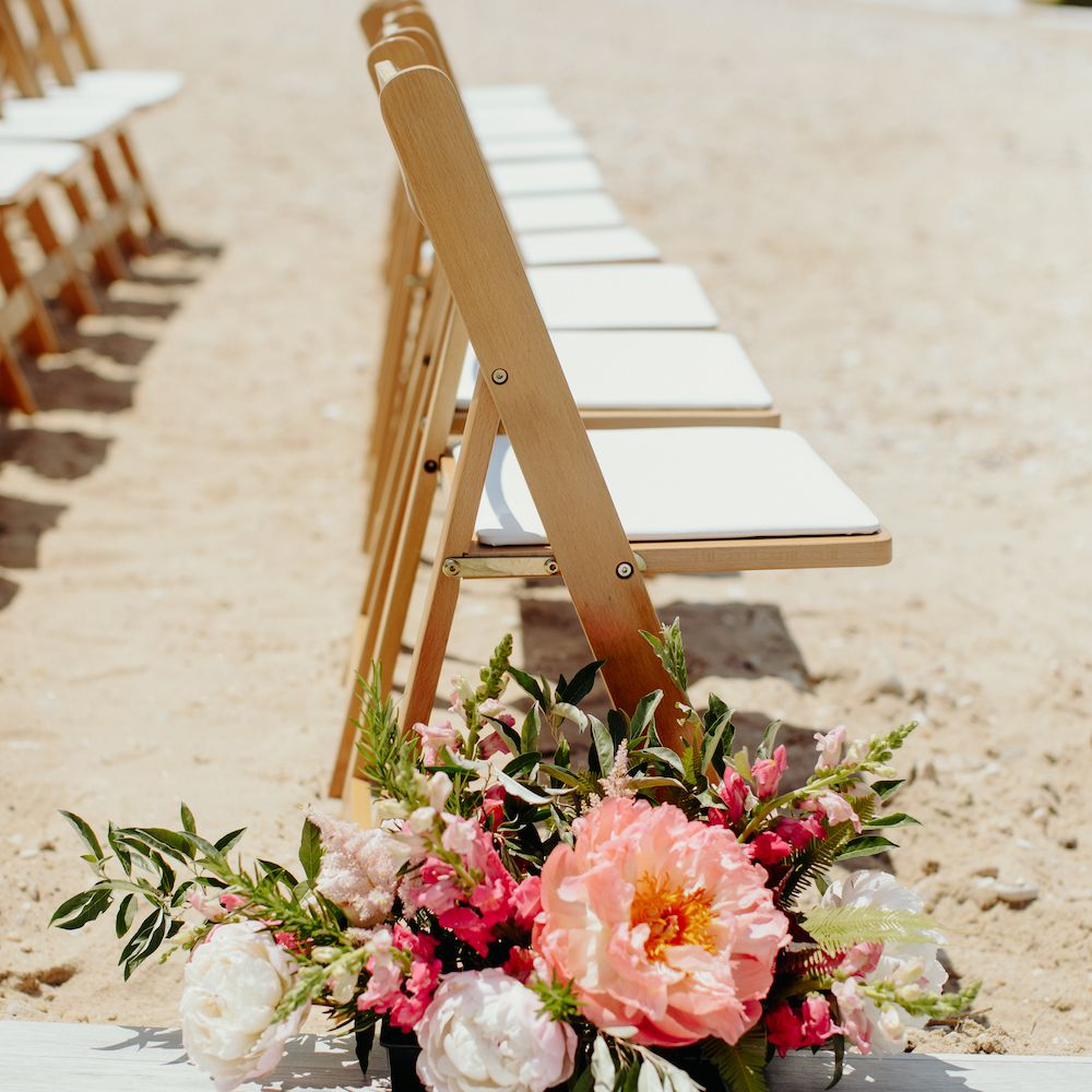 Folding wood wedding aisle chairs with behind flower arrangement