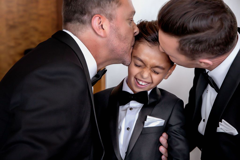 two fathers kissing son's forehead