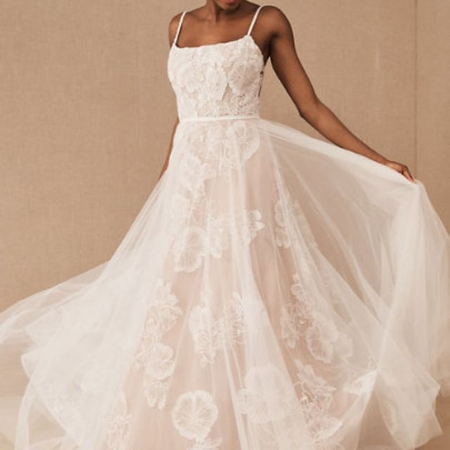 Model in thin strapped A-line white floral lace wedding gown