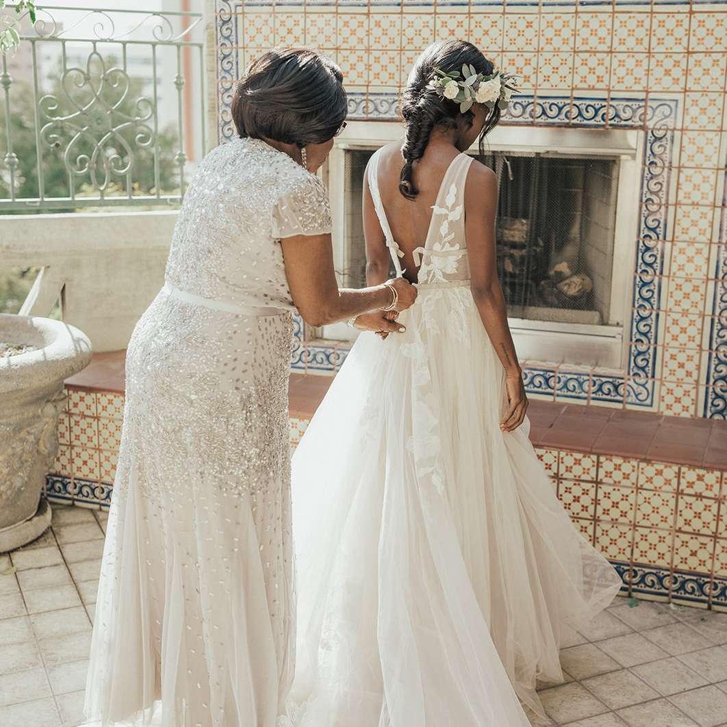 mother zipping bride's wedding dress