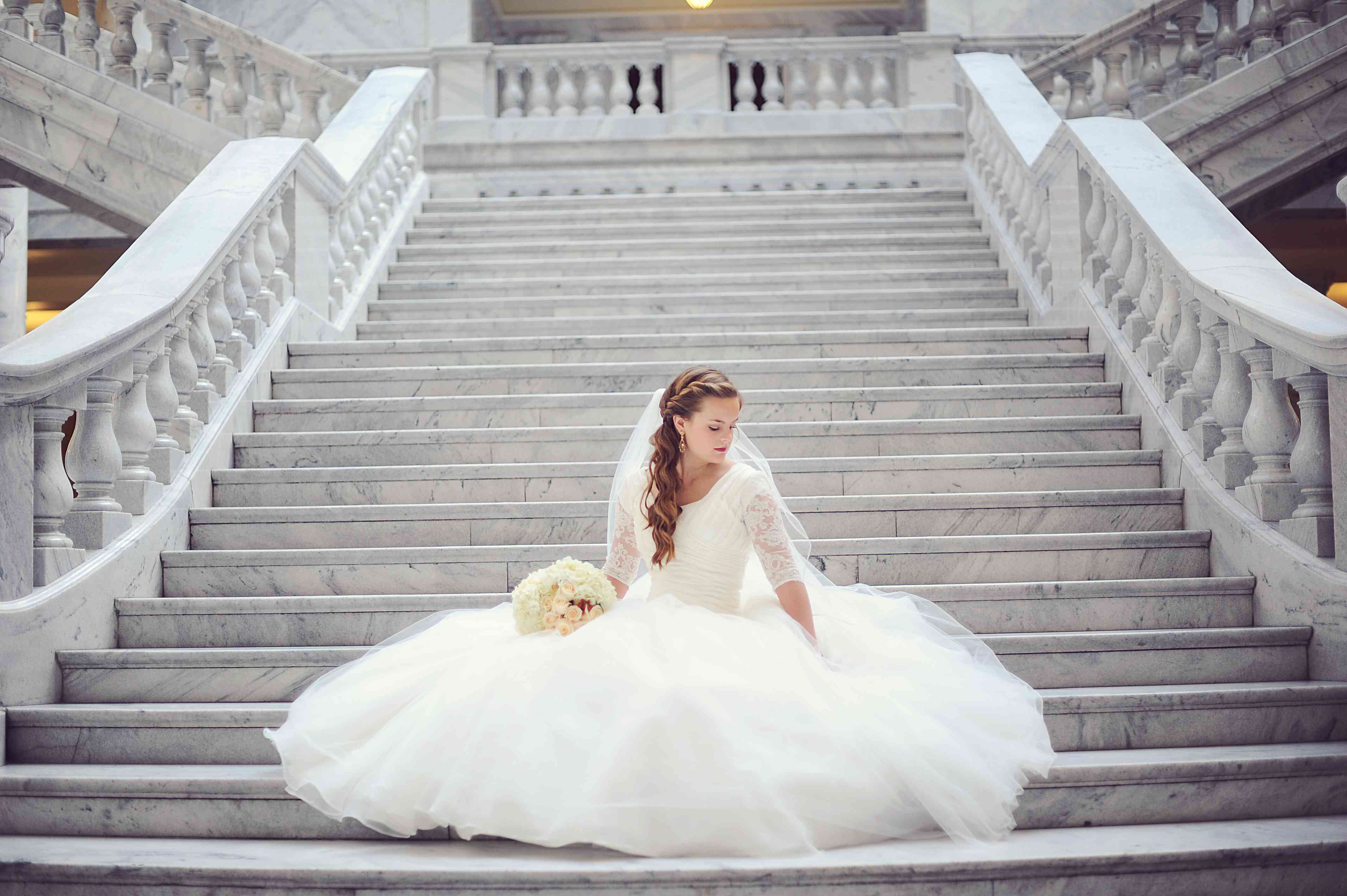Bride Sitting on Staircase in Wedding Dress