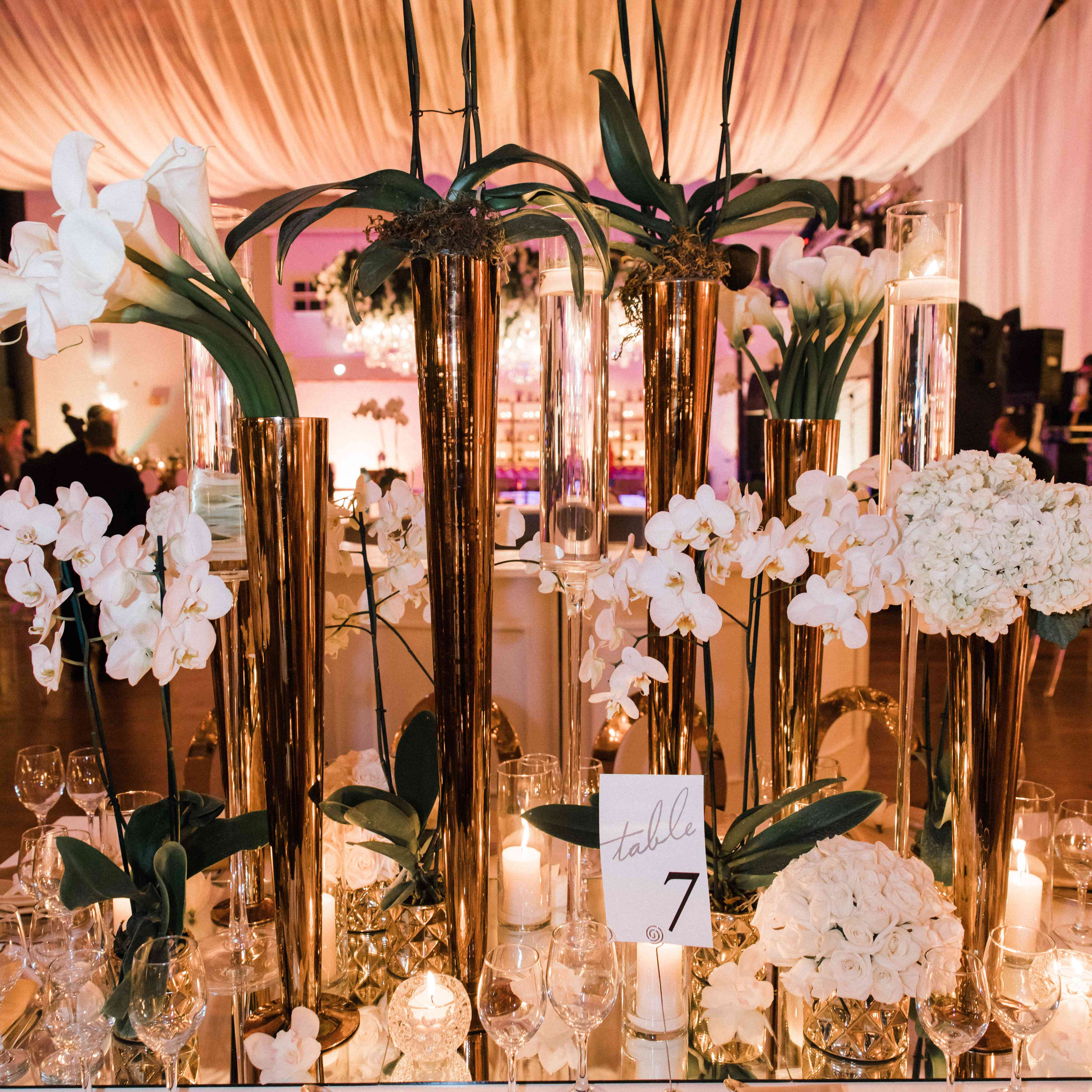 <p>mirrored centerpieces tall gold vases white flowers</p><br><br>