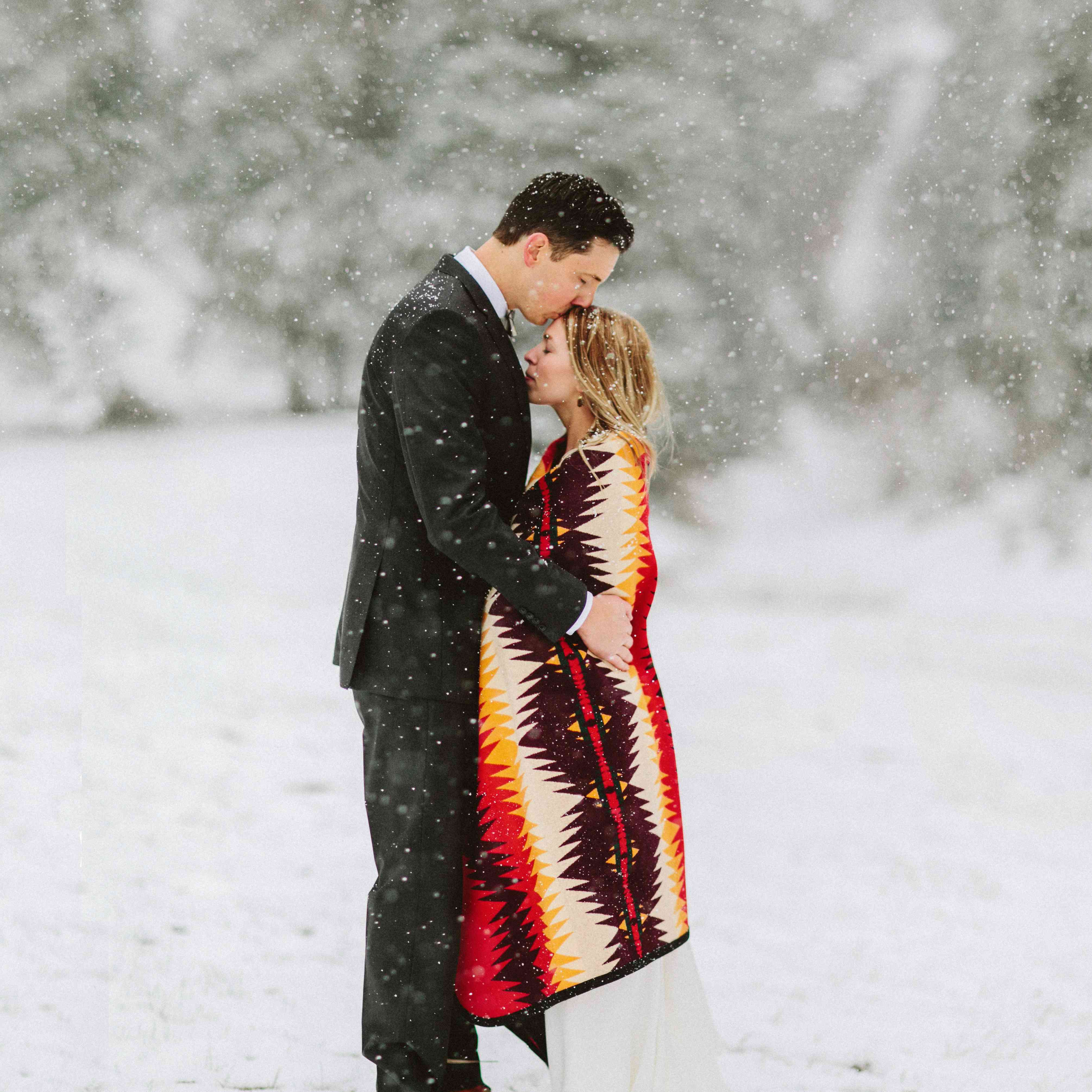 Groom kissing bride's forehead outside in the snow while bride is wrapped in colorful blanket