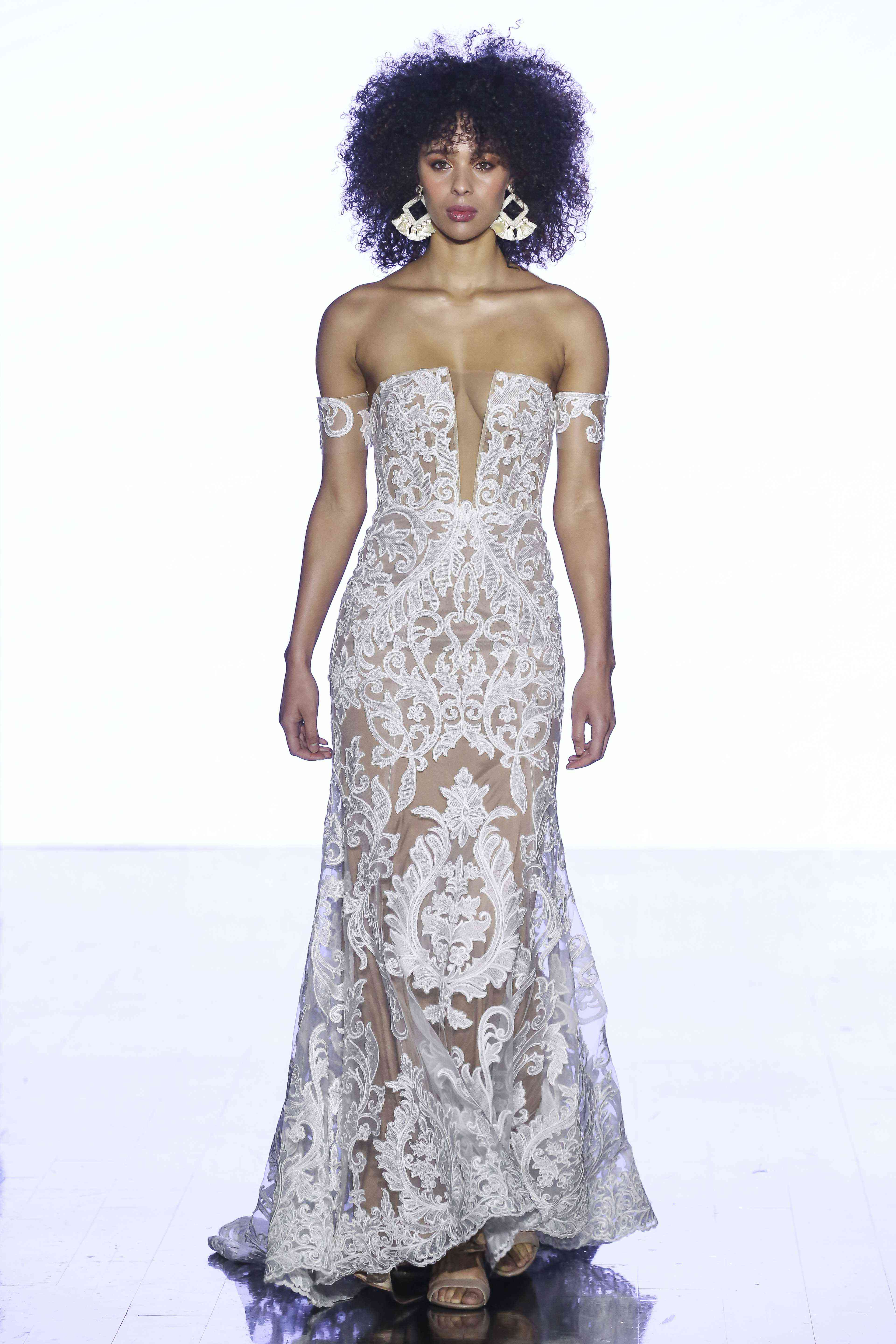 Model in allover lace sheath gown with a plunging illusion neckline and matching armbands
