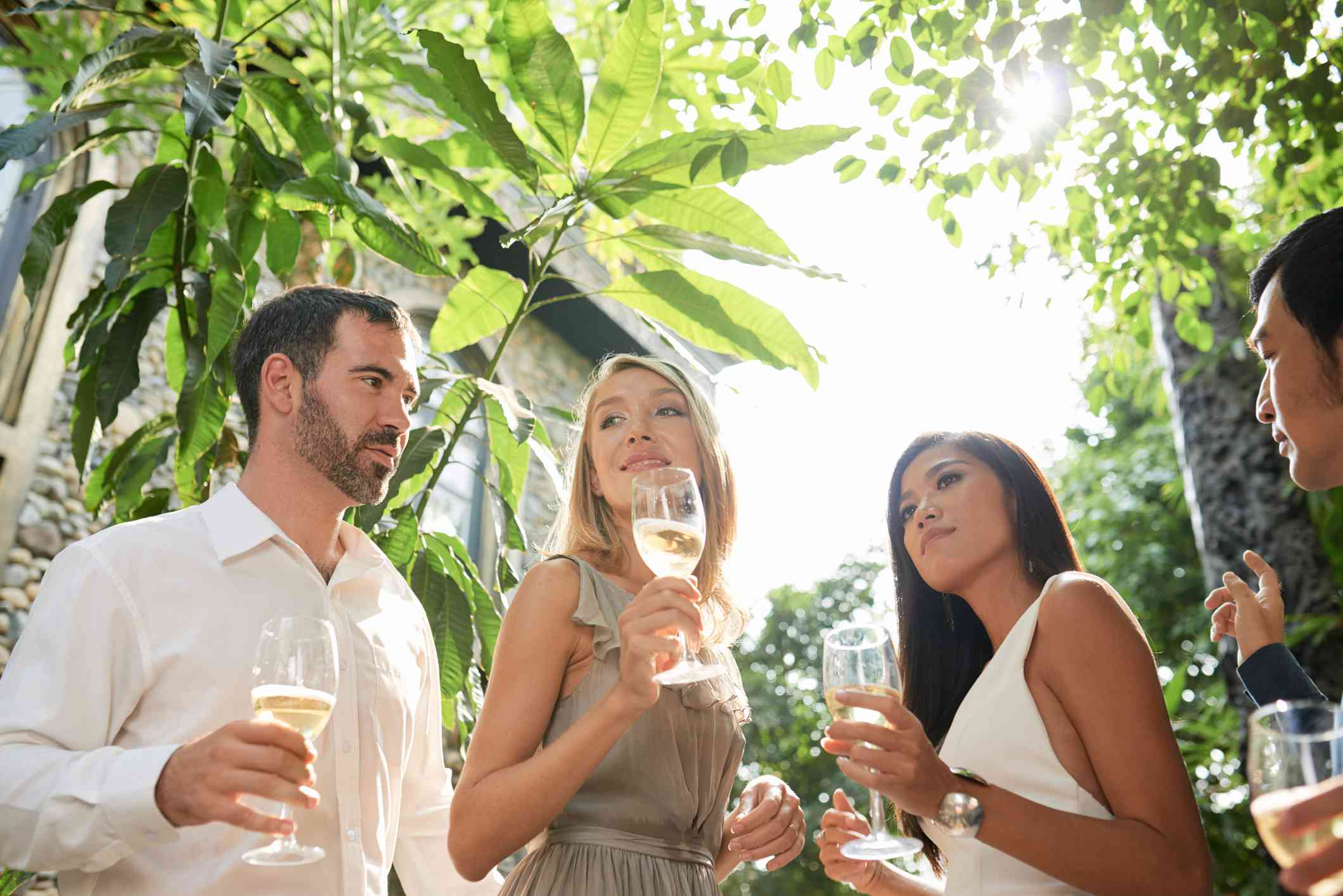 Two women and two men in formal attire drinking champagne outside