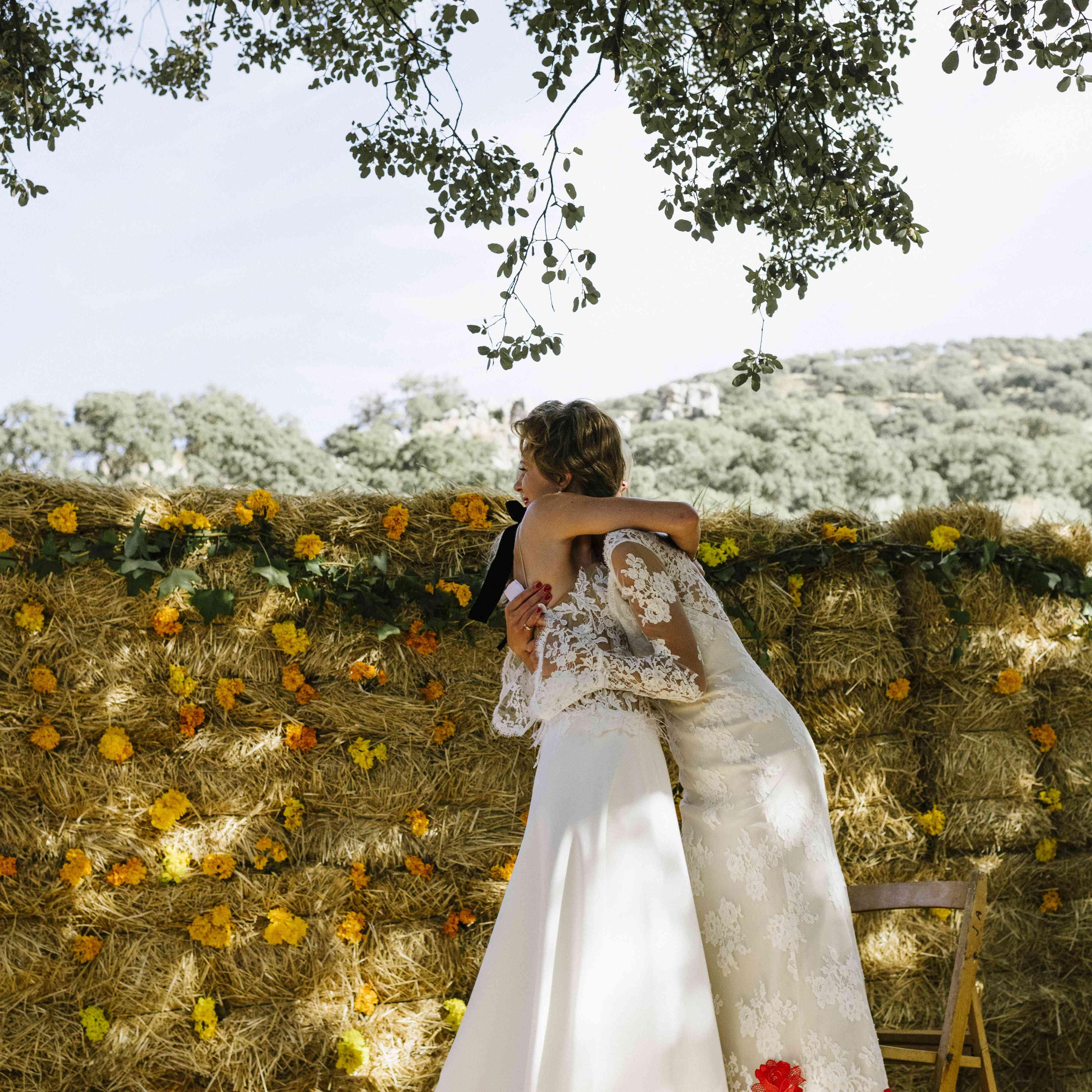 ceremony brides hugging at altar