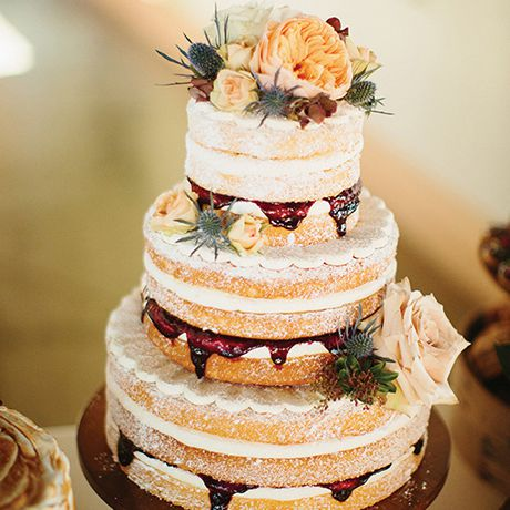 A rustic naked wedding cake by Cakewalk Bake Shop with a dusting of powdered sugar and dripping with jam filling