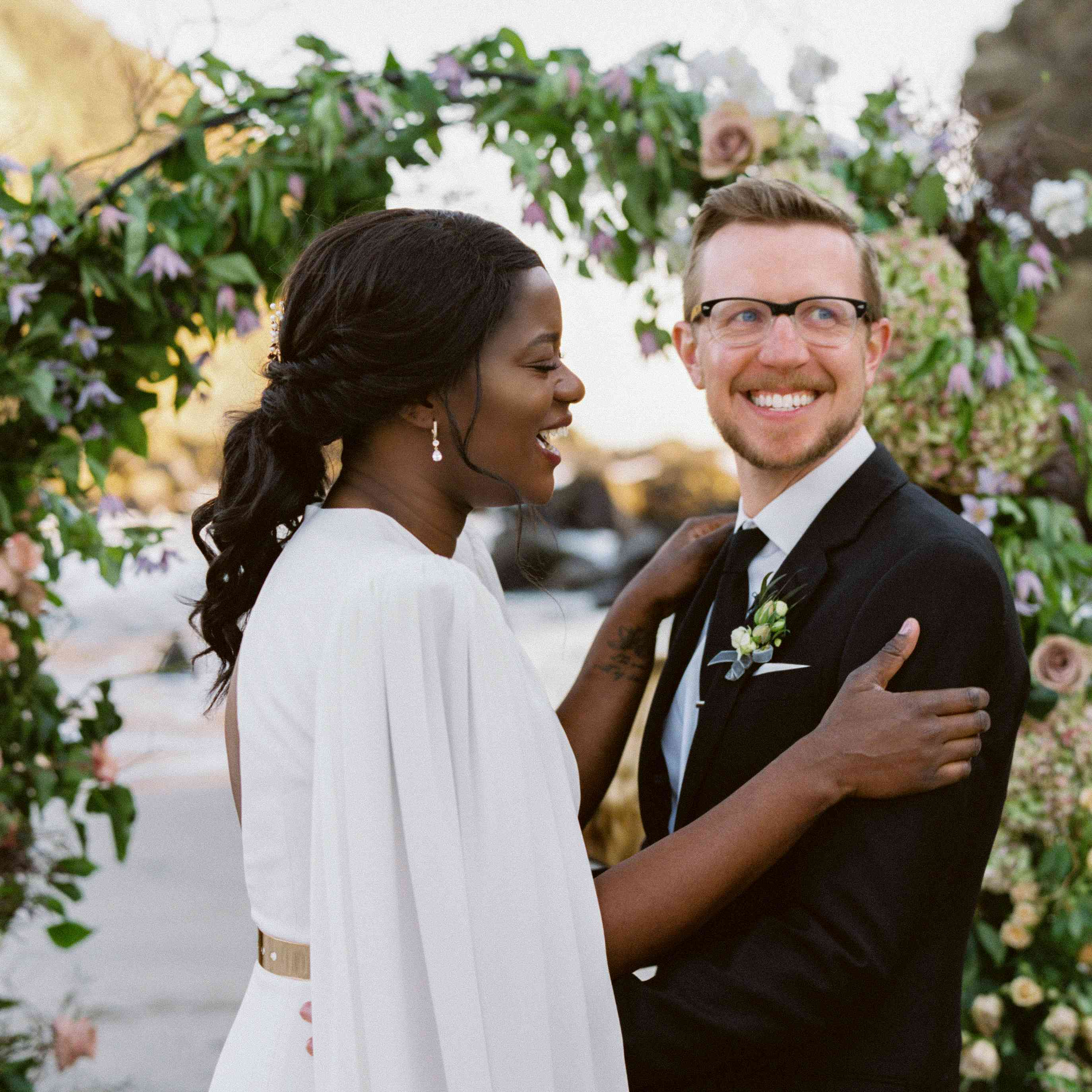Laughing bride and groom in front of floral arch