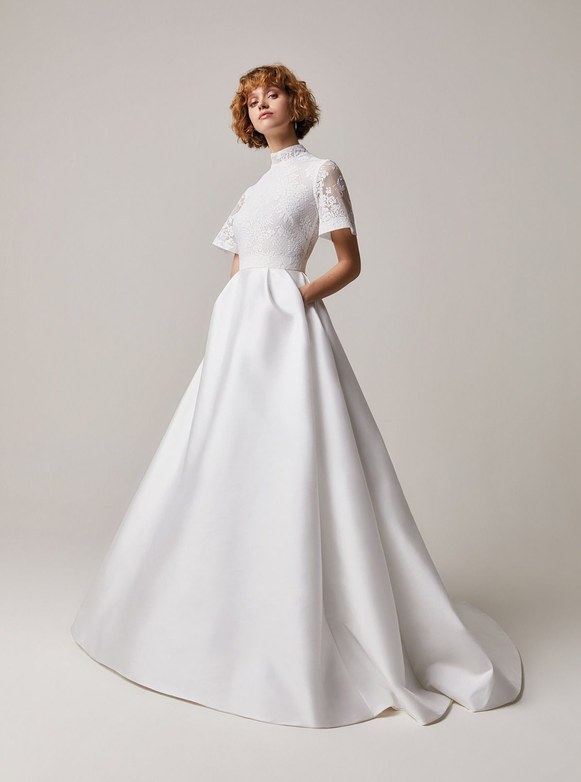 Model in high-neck white wedding gown with pockets