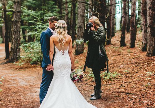photographer taking wedding photos in woods